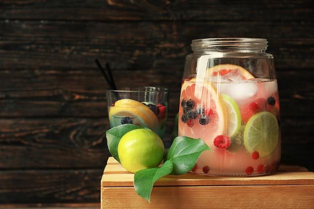 Smaczna lemoniada z cytrusami i jagodami w szklanych naczyniach na drewnianej skrzynce