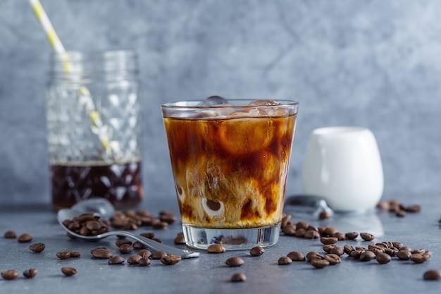 Smaczna orzeźwiająca kawa mrożona z kostkami lodu w okularach na jasnym tle. zbliżenie