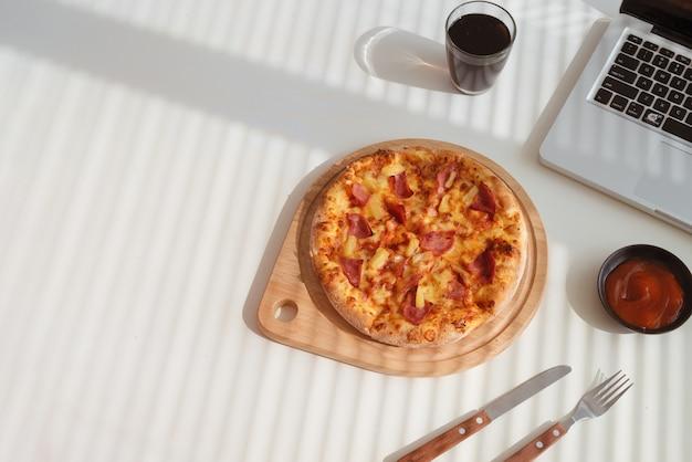 Smaczna pizza na biurku z colą i laptopem, fast food