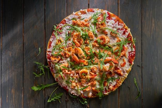 Smaczna pizza z krewetkami i rukolą na drewnianym stole. widok z góry.
