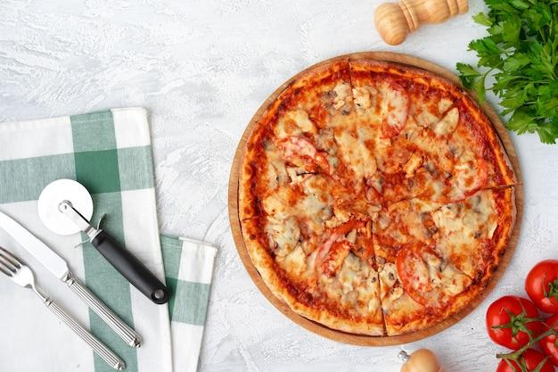 Smaczna pizza z kurczakiem i grzybami, widok z góry na szarym tle