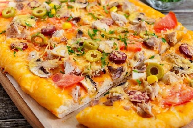 Smaczna pizza z pieczarkami, kurczakiem, pepperoni, oliwkami, kukurydzą pokrojoną na kawałki