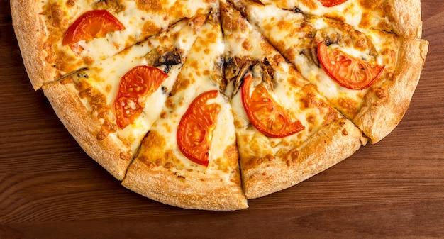 Smaczna pizza z pomidorów, serów i aromatycznych pieczarek na drewnianym stole. widok z góry