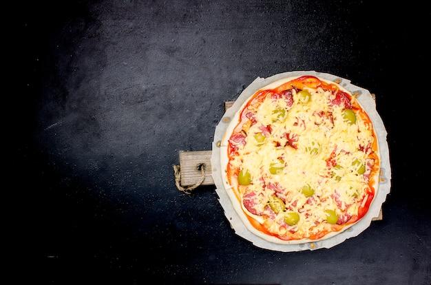 Smaczna pizza z przyprawami i oliwkami na czarnym tle