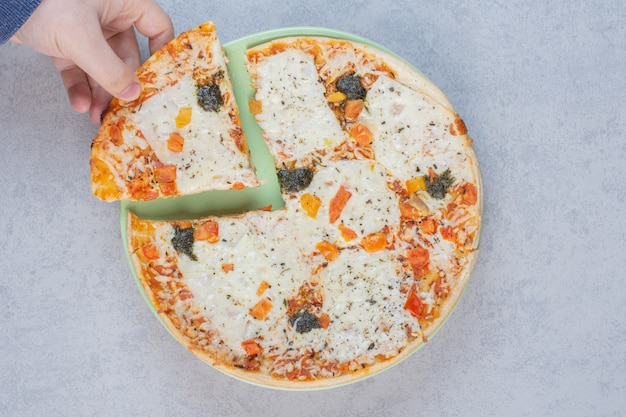 Smaczna pizza z solonymi ogórkami i serem na szarym tle.