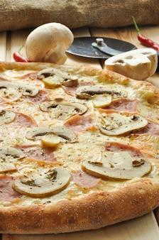 Smaczna pizza z szynką i pieczarkami na drewnianym stole