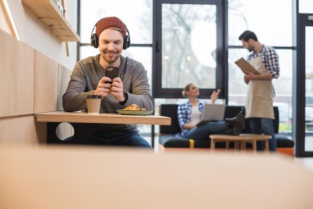 Smaczna przekąska. przyjemny, pozytywny, przystojny mężczyzna siedzi przy stoliku w kawiarni i używa swojego smartfona, jedząc smaczną przekąskę