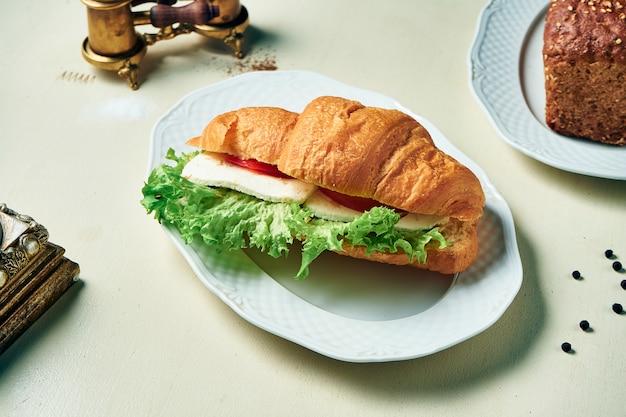 Smaczna przekąska - rogalik z kurczakiem, serem, pomidorami i sałatą na białym talerzu i białym drewnianym stole. zamknąć widok.