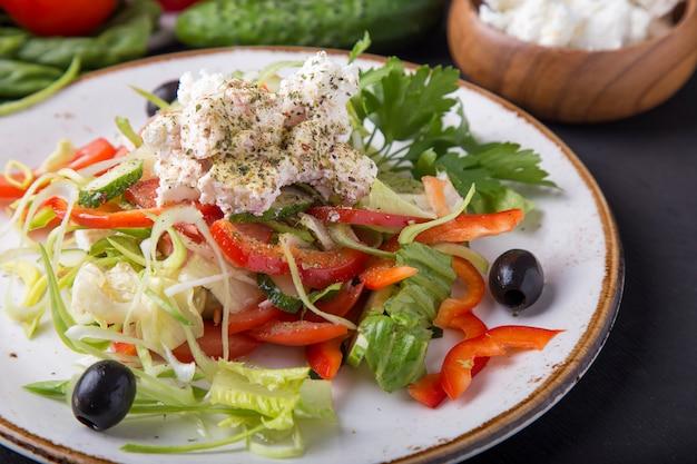 Smaczna sałatka grecka ze świeżymi warzywami, serem feta i czarnymi oliwkami