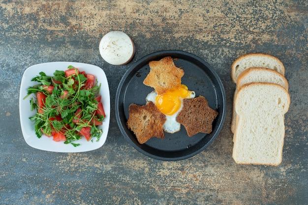 Smaczna sałatka z krojonym pieczywem i gotowanymi jajkami na marmurowym tle