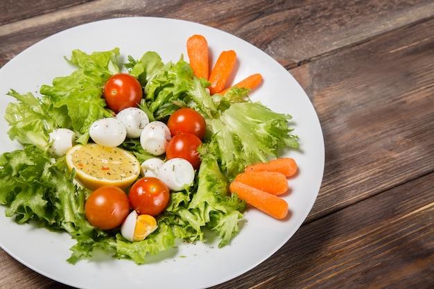 Smaczna sałatka z pomidorami koktajlowymi, liśćmi sałaty, cytryną, przyprawami, jajkami marchewki i przepiórki na drewnianym stole