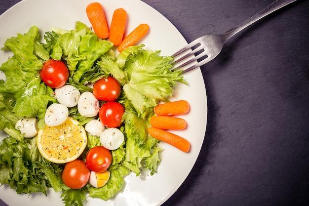 Smaczna sałatka z pomidorami koktajlowymi, liśćmi sałaty, cytryną, przyprawami, marchewką i jajkami przepiórczymi na kamiennym stole z widelcem
