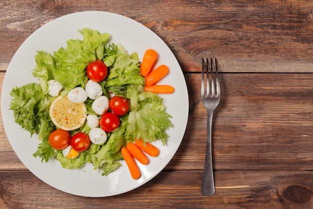 Smaczna sałatka z pomidorkami cherry, liśćmi sałaty, cytryną, przyprawami, marchewką i jajkami przepiórczymi na drewnianym stole z widelcem