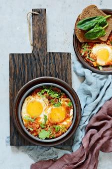 Smaczna shakshuka, jajka sadzone w sosie pomidorowym na wielkanocny brunch.