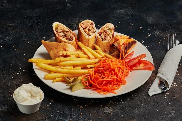 Smaczna shawarma ze smażonymi ziemniakami na ciemnym tle