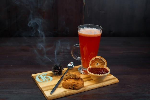 Smaczna słodka gorąca czerwona herbata z dżemem truskawkowym i ciasteczkami owsianymi stoi na drewnianym stole vintage w kawiarni. słodki ciepły napój rozgrzewający. przytulna atmosfera.