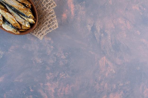 Smaczna solona ryba na drewnianym talerzu na marmurowej powierzchni