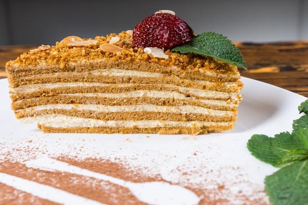 Smaczna specjalność przekładana tarta z biszkoptem i śmietanką zwieńczona świeżą truskawką podana na talerzu z dekoracją w proszku czekoladowym