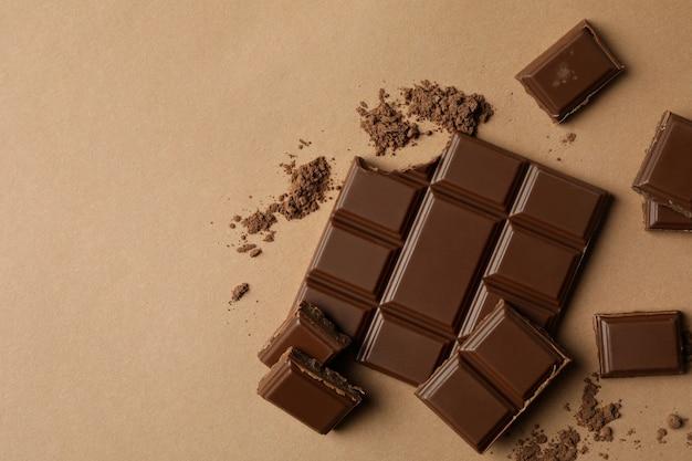 Smaczna tabliczka czekolady i proszek na beżowym tle