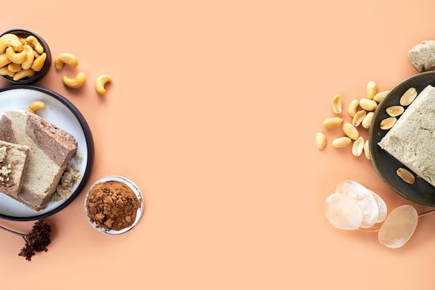 Smaczna wschodnia słodka chałwa deserowa z kakao i orzechów nerkowca na beżowym tletradycyjny deser