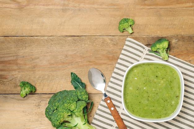 Smaczna zupa brokułowa na drewnianym tle