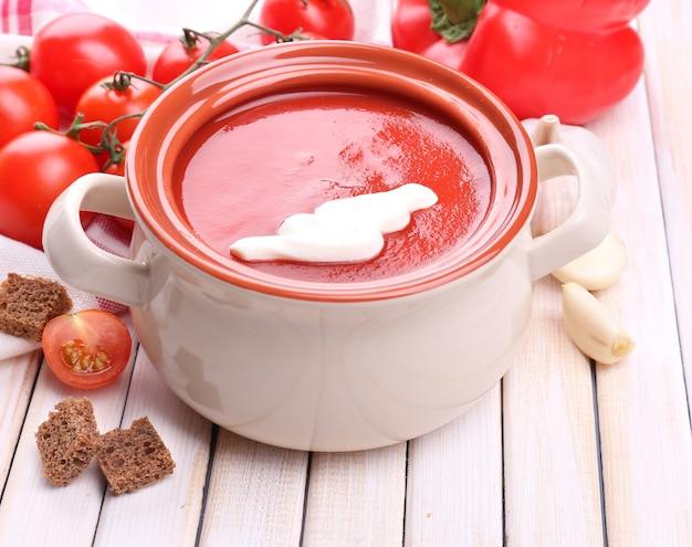 Smaczna zupa pomidorowa i warzywa na drewnianym stole