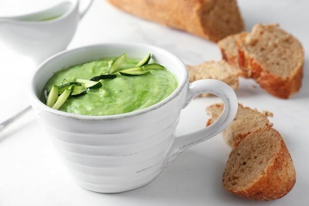 Smaczna zupa z cukinii w filiżance z chlebem na podświetlanym stole