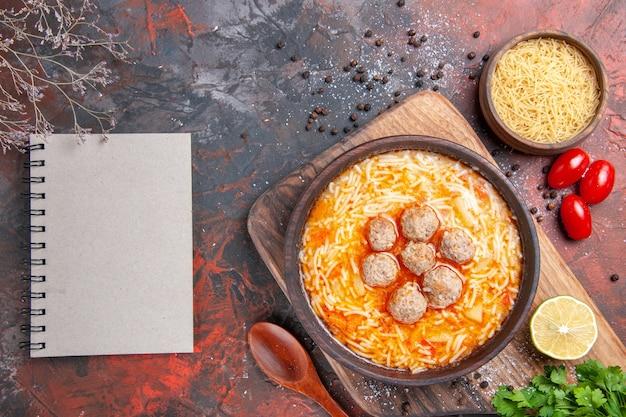 Smaczna zupa z klopsikami z makaronem na desce cytrynowy drewniany makaron pęczek zielonych pomidorów pieprz i notatnik na ciemnym stole