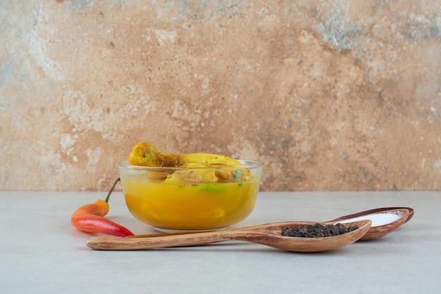 Smaczna zupa z przyprawami i papryczką chili na białym stole.