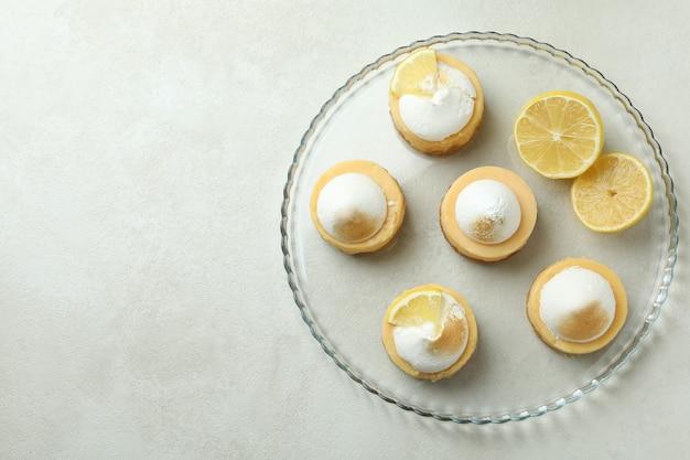Smaczne babeczki cytrynowe na tacy na białym stole z teksturą
