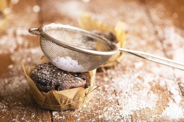 Smaczne babeczki czekoladowe w cukrze pudrem na stole