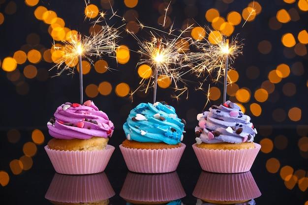 Smaczne babeczki urodzinowe na stole przed nieostre światła