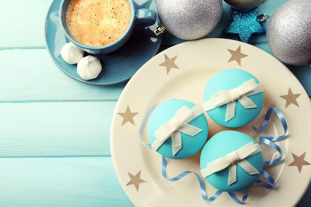 Smaczne babeczki z kokardką, filiżanką kawy i świątecznymi zabawkami na kolorowej drewnianej powierzchni