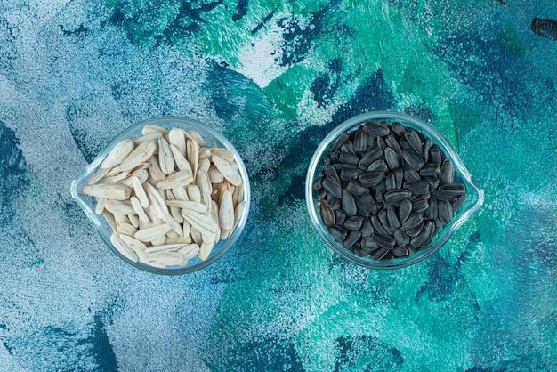 Smaczne białe i czarne nasiona słonecznika w szklanych miseczkach, na niebieskim stole.