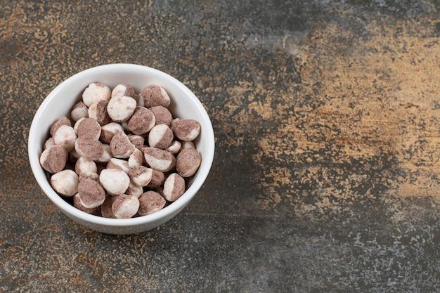 Smaczne brązowe cukierki w białej misce.