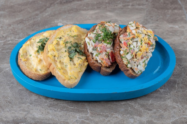 Smaczne bruschetty z jajkami i warzywami na niebieskim talerzu.