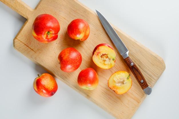 Smaczne brzoskwinie z nożem owocowym w desce do krojenia na białej powierzchni, leżą płasko.