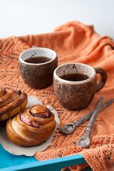 Smaczne bułeczki z dżemem i dwiema filiżankami herbaty na niebieskim drewnie.