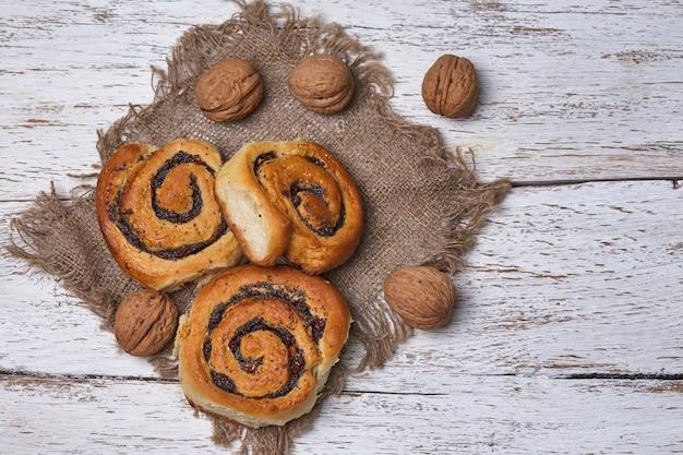 Smaczne bułeczki z rodzynkami na białym rustykalnym drewnianym stole. świeża piekarnia. śniadanie. chleb. widok z góry