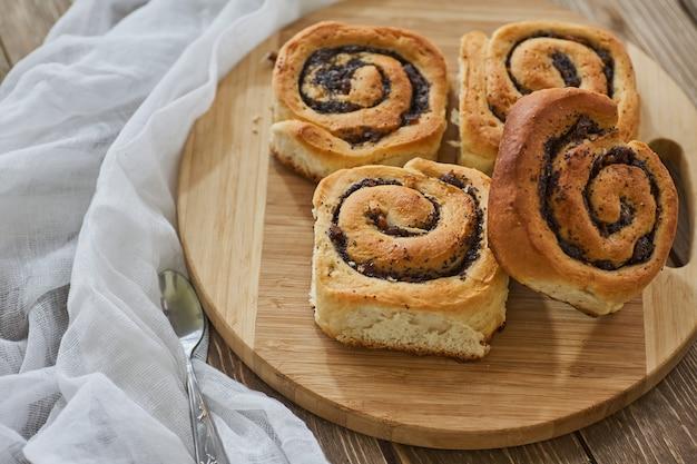 Smaczne bułeczki z rodzynkami na brązowym rustykalnym drewnianym stole. świeża piekarnia. śniadanie. chleb. widok z góry