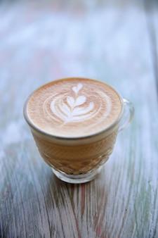 Smaczne cappuccino jest na drewnianym stole z teksturą z tłem natury