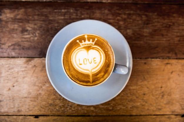 Smaczne cappuccino znajduje się na drewnianym stole z teksturą z miłosną sztuką