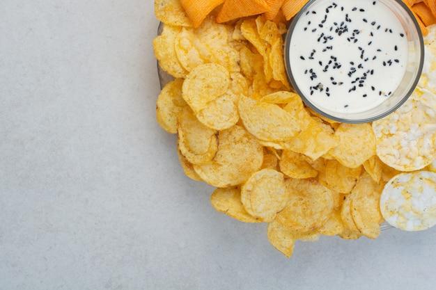 Smaczne chipsy ziemniaczane crucnhy z jogurtem na białym tle. wysokiej jakości zdjęcie
