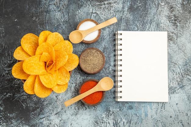Smaczne chipsy ziemniaczane ozdobione różnymi przyprawami w kształcie kwiatów z łyżeczkami na szarym tle