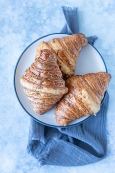 Smaczne chrupiące rogaliki, betonowe niebieskie tło. piekarnia na śniadanie. selektywne skupienie.