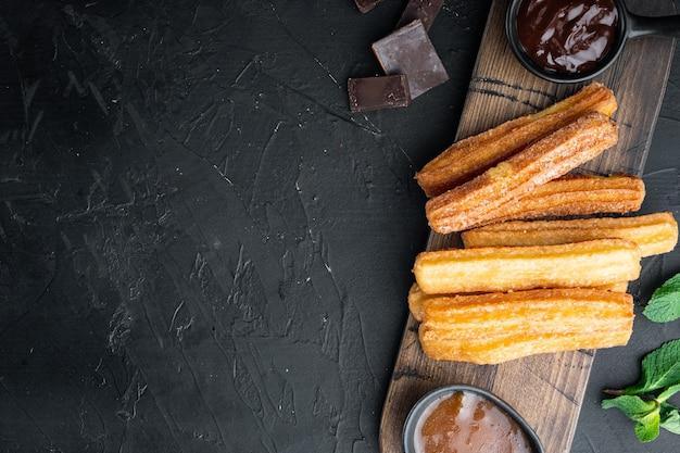 Smaczne churros z zestawem sosu czekoladowo-karmelowego, na czarnym tle, widok z góry płasko leżał z miejscem na tekst, copyspace