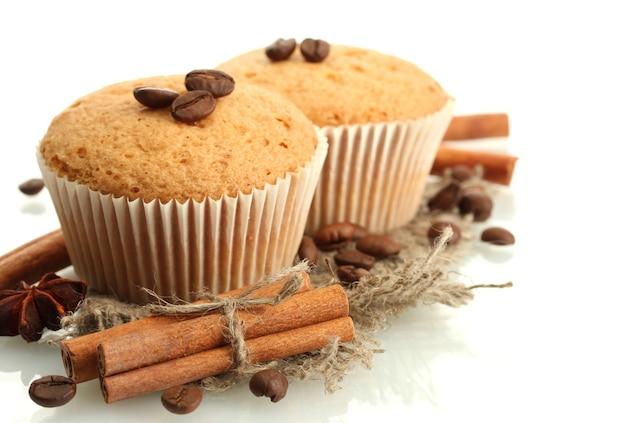 Smaczne ciasta muffinki na jucie, przyprawach i ziarnach kawy, na białym tle