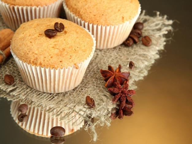 Smaczne ciasta muffinki na jucie, przyprawach i ziarnach kawy, na brązowym tle