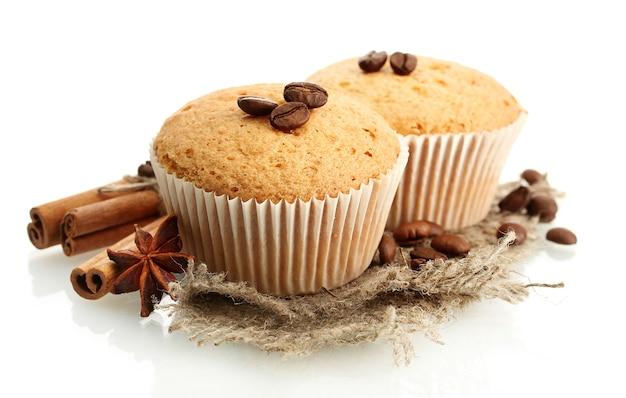 Smaczne ciasta muffinki na płótnie, przyprawach i ziarnach kawy, na białym tle