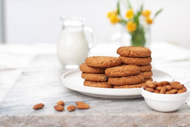 Smaczne ciasteczka owsiane i migdałowe ze słoikiem mleka na starym marmurowym stole